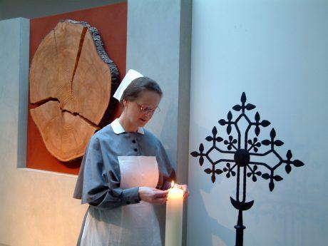 Schwester Renate zündet Kerze an