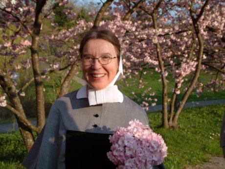Schwester umgeben von Blumen auf einer Wiese